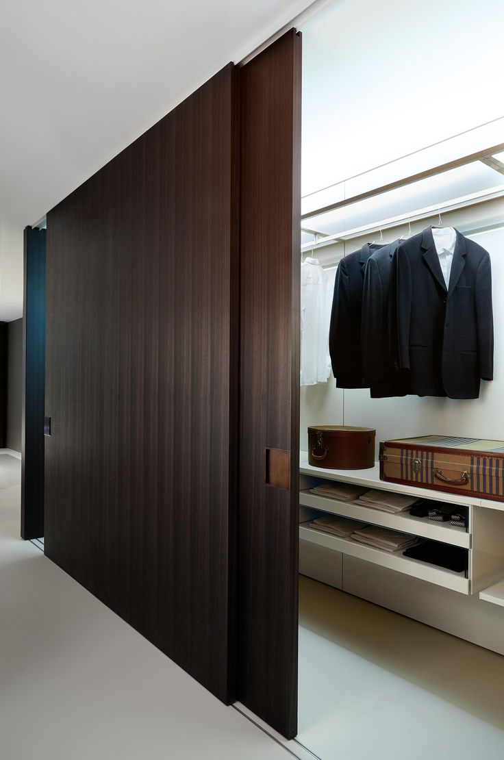 Closet concept: blackish-brown stained full ceiling height sliding door with an extra foot of depth makes it a hybrid walk in/sliding closet.