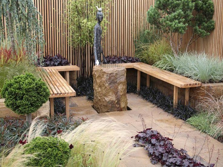 jardín pequeño con bancos de madera y piedra grande decorativa