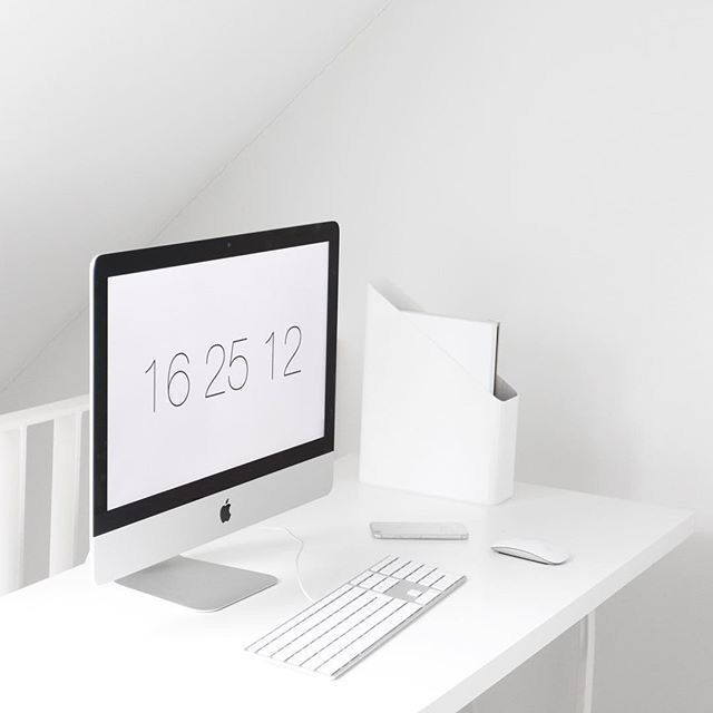 White home office with white type pad, Apple computer, white desk