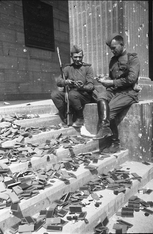 ПОБЕДА! Советские солдаты, отдыхая на ступенях рейхсканцелярии, рассматривают немецкие награды, которые так и не были вручены. Берлин. 2 мая 1945 года.