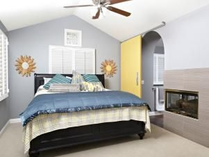 A comfortable and cheery bedroom in neutral tones offers plantation shutters and a wall fireplace which it  shares with the bathroom. A yellow sliding barn door and arched doorway are unique features of this bedroom.