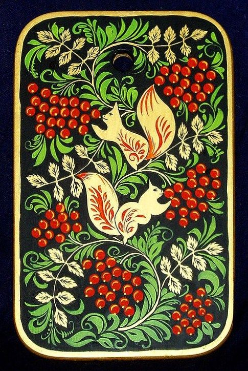 A wooden chopping board with folk Khokhloma painting from Russia. A pattern with squirrels eating Rowan berries.