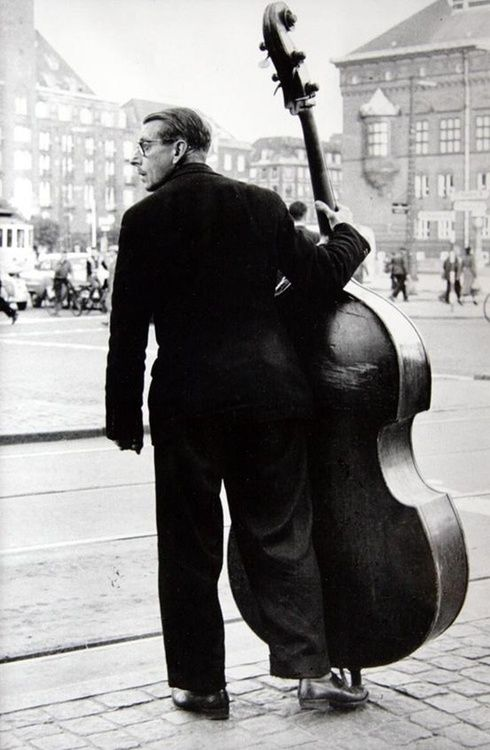 """""""With a double bass to the townhall place."""" Denmark. 1956. Photographer: Toni Schneiders"""