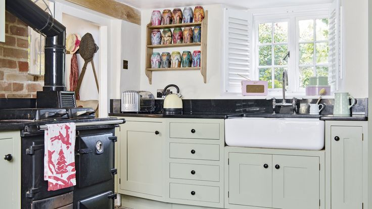 Black marble worktops and iron handles tie the strong colour into the scheme and green painted units make an attractive contrast in this charming country kitchen