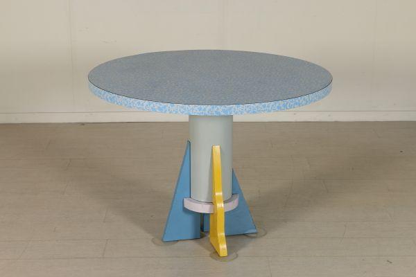Tavolo che nello stile ricorda il movimento fondato negli anni 70 da Ettore Sottsass; legno ricoperto in formica, base in metallo. Buone condizioni, presenta piccoli segni di usura.