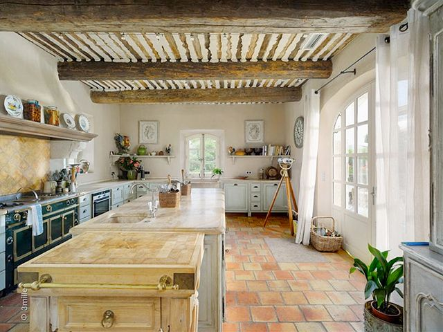 french country kitchen with tile floors and island with sink