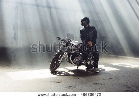 Sexy biker man wearing jeans and leather jacket sitting on vintage custom motorcycle. Urban scene