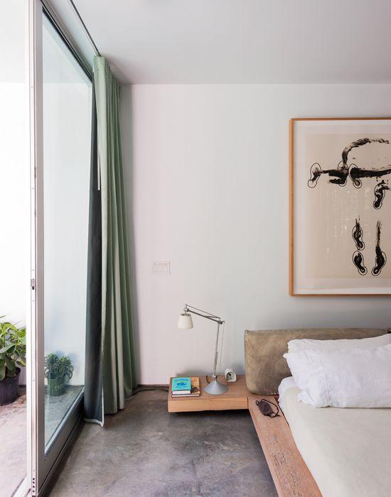 Nella camera padronale, affacciata sulla piscina, il letto matrimoniale ha una base in legno che funge anche da pratico comodino. La testiera fatta di grandi cuscini di stoffa, rende l'insieme morbido e elegante