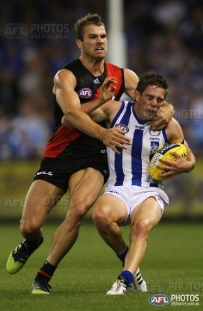Essendon's Stewart Crameri tackles North Melbourne's Ryan Bastinac during the AFL Round 01 match between the North Melbourne Kangaroos and the Essendon Bombers at Etihad Stadium, Melbourne. (Photo: Andrew White/AFL Media)