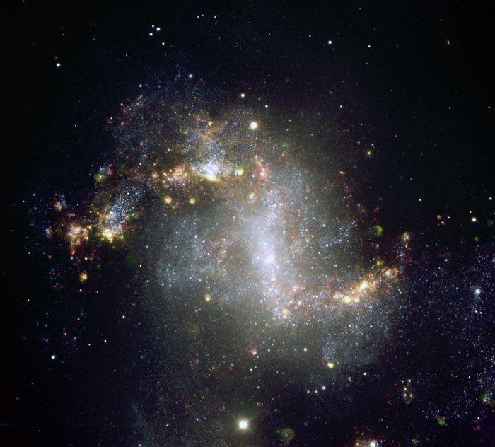 Starburst-Galaxie NGC 1313. Diese Galaxie befindet sich in einem Zustand aktiver Sternentstehung; dementsprechend deutlich zeigt das Bild eine Vielzahl von Sternentstehungsregionen. Außerdem sind eine größere Anzahl ausgedehnter Gashüllen sichtbar, die sich bei den wiederkehrenden Ausbrüchen der Sternentstehung bilden.