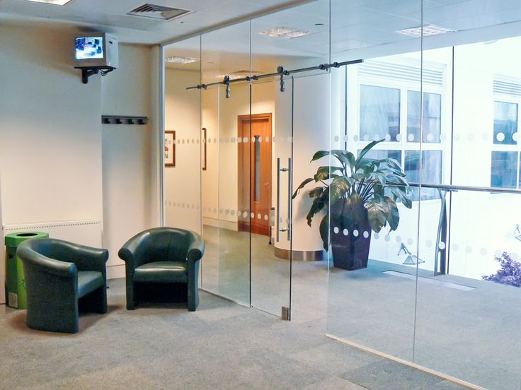 01 - Impressive office formed from full height frameless glass partitioning with glass sliding door
