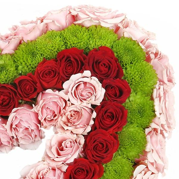 A handcrafted flower heart made of pink and red spray roses and green pom-pom chrysanthemums. Made out of fresh and beautiful flowers, this is a symbol of love.  Loving You - Roses - Flower Delivery NYC - plantshed.com