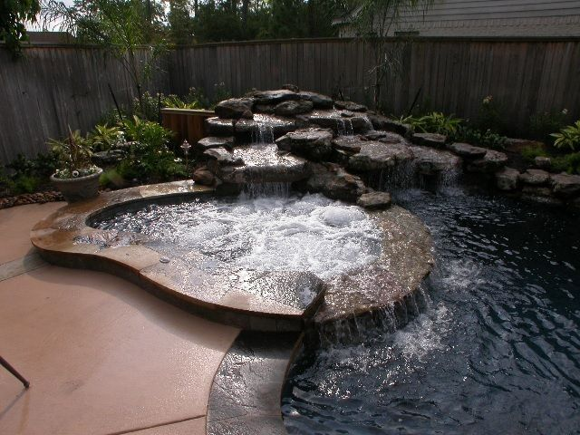 Mediterranean Hot Tub with Pool with hot tub, Concrete floors, Fence, Water feature, Pool waterfall feature