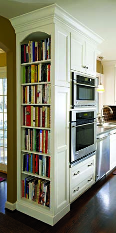 """A tall shelf built into kitchen cabinets puts cookbooks within easy reach, and their colorful spines help brighten up the all-white decor."""