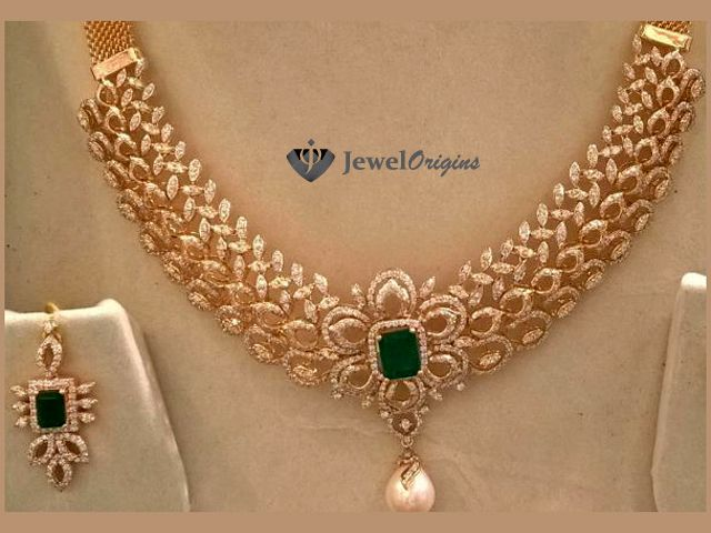 Diamond necklace and earrings set, studded with diamonds and emeralds with pearl drop in necklace, in 18 carat gold.