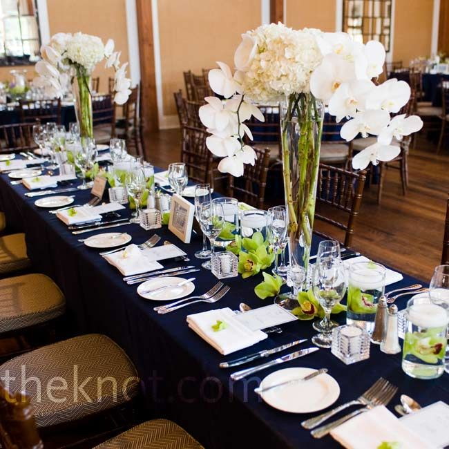 Tall vases of hydrangeas and orchids topped the long head for White wedding table decorations