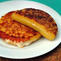 "Arepas – Cuban Corn ""Pancake"" Sandwiches - The famous corn pancake sandwich served at fairs and exhibits in Miami – two cornmeal ""cakes"" with a layer of gooey cheese inside."