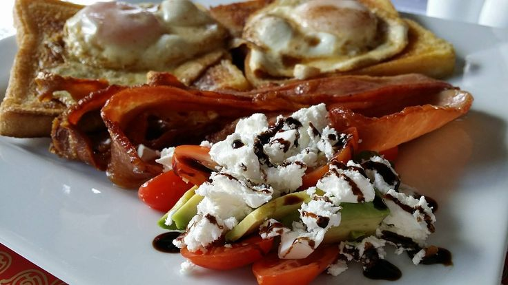 Bacon and eggs with tomato, avocado, danish feta side salad with balsamic glaze. Egg's fried sunny side up in butter.
