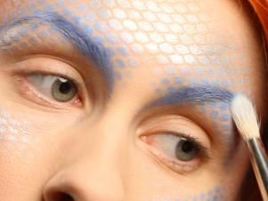 Detail eyebrows with a brush and blue creme foundation, then set it with a touch of shadow.