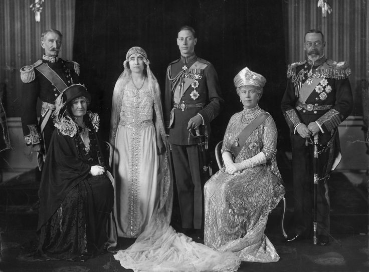 In this photograph: King George V of Great Britain (right) and Queen Mary. Center are the future King George VI and Elizabeth Bowes-Lyon. On the left are the Earl and Countess of Strathmore, Elizabeth's parents.