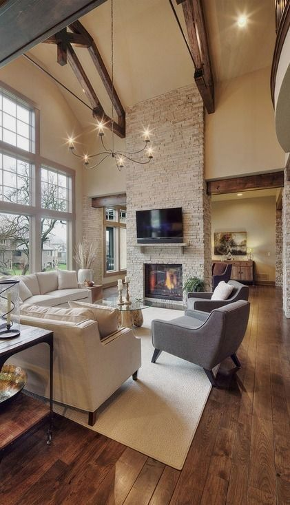#homedesign #livingroomdecor #inspiration | Photo of a rustic family room in Kansas City with beige walls, dark hardwood floors, a standard fireplace, a stone fireplace surround and a wall-mounted tv. — Houzz