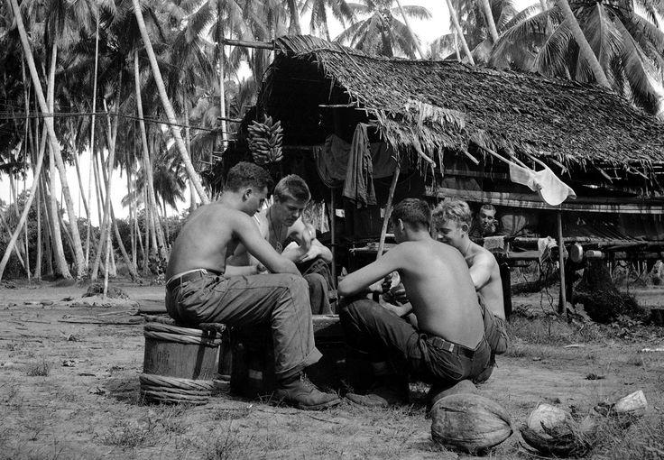 Американские солдаты из разных штатов на войне. Здесь, после боёв, солдаты (двое из Детройта) расслабились за игрой в карты, в пальмовой роще в тылу, Буна, Новая Гвинея, 13 января 1943 г. Игроки, слева направо: рядовой Сэм Демополис, Детройт, Мичиган; рядовой Роберт Труделл (лицом к камере), Детройт; капрал Джеймс Уильямс (спиной к камере); Genesee Depot, Висконсин; и рядовой Лоуренс Томпсон, Дулут, штат Миннесота | AP Photo / Ed Widdis