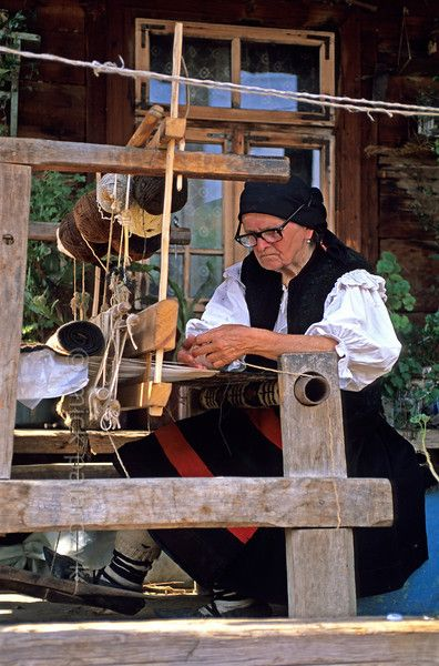 [ROMANIA.MARAMURES 23.658] Working on an old loom in front of her house this inhabitant of Botiza village uses wool that has been coloured by plant extracts. - Tesutul la razboi, Romania