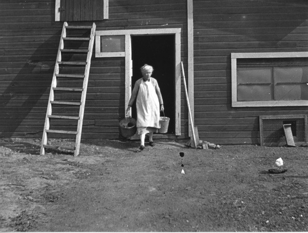Woman carrying empty pails from her barn | saskhistoryonline.ca
