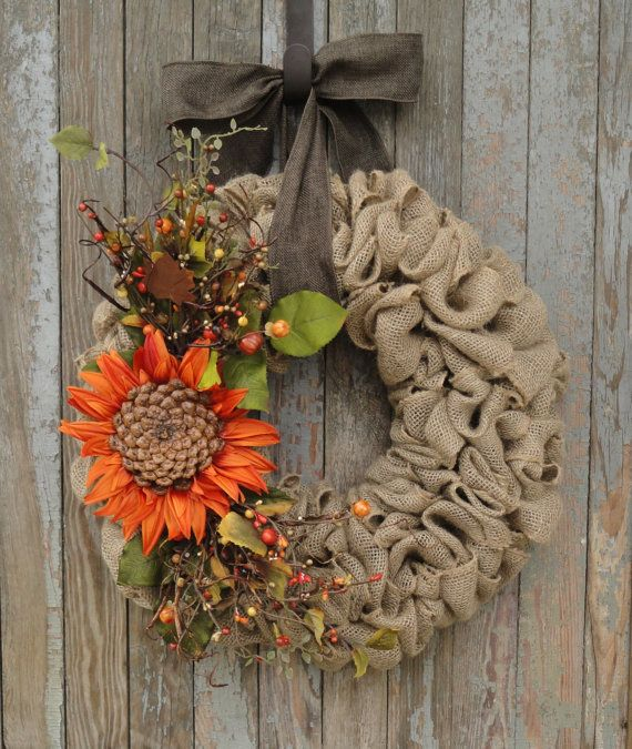 Welcome all your friends to your home with this warm and inviting Fall Burlap Wreath. Natural burlap wreath with a large unique sunflower. Sunflower has a center made of a natural pine cone base. Accented with berries and small pumpkin berry picks; (all with fall colors; brown and orange tones), curly willow twigs, greenery, and a rusty maple leaf pick to make this a beautiful rustic fall wreath. Hangs from a brown faux burlap or an orange, natural, and brown striped canvas ribbon bow. Our…