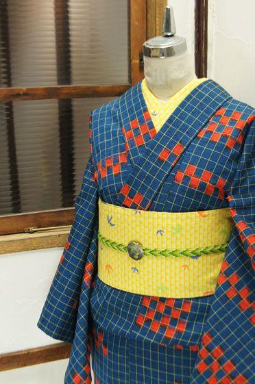 ほのかに緑を帯びた青に、キャロットオレンジの市松パターンが織り出されたレトロモダンなウールのアンサンブル(羽織と着物のセット)です。