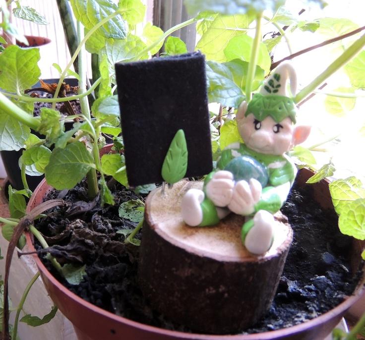 Gnomo da Saúde - criatura mitológica elemental da terra que cuida da saúde, sentada em meio ao hortelã. Carrega um cristal (ágata verde) que o auxilia a trazer saúde a seu dono