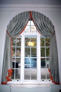Fixed headed curtains in arched window