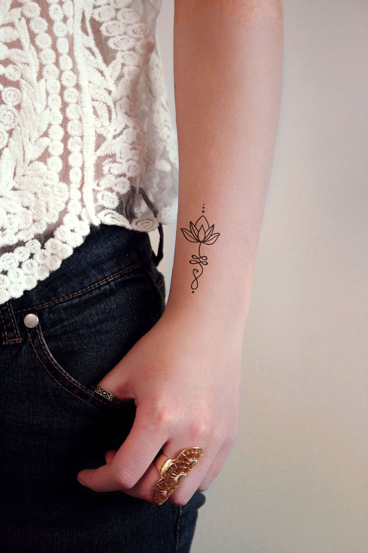 A pretty unalome tattoo with a lotus flower on top. It symbolizes the journey to enlightenment and the opportunity of new beginnings through struggles. To find or path requires strength and divine int