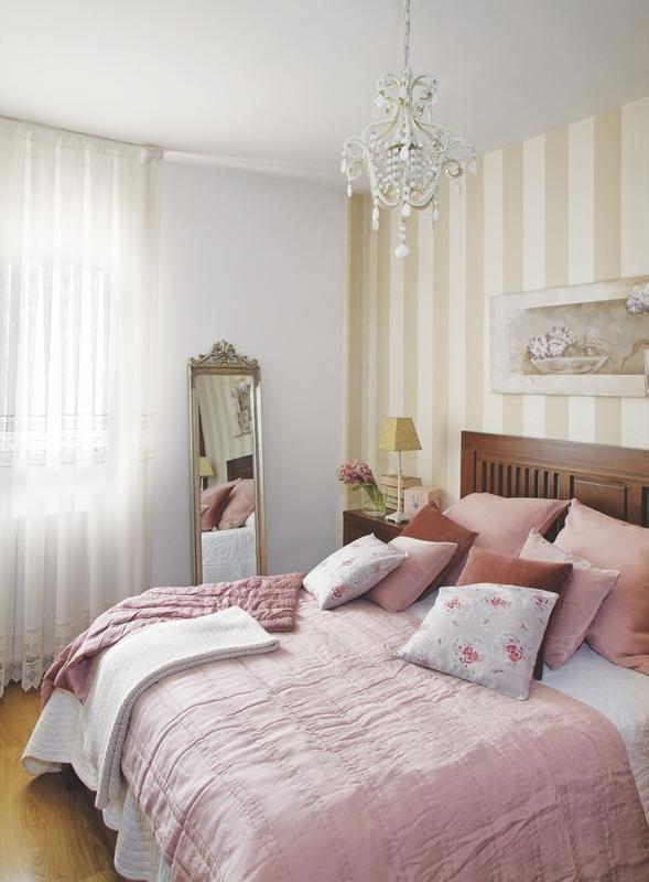 Dormitorio romántico con papel a rayas en la pared y espejo clásico