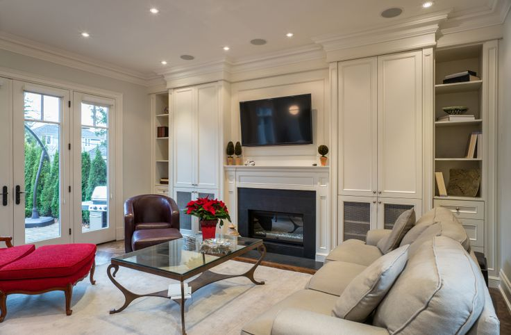 Second angle on the same living room; here we see the built in cabinetry and bookshelves flanking the fireplace in full. Patio is seen at left through all glass doors.