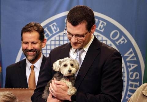 Sen. Joe Fain holds his dog, Waffles, as Gov. Jay Inslee signed in May a bill Fain sponsored that expanded the state's animal cruelty laws in Olympia. The measure makes it a civil offense to lock an animal in a car or enclosed space in dangerous conditions, like extreme heat or cold. The FBI will begin tracking cases of animal cruelty nationally in 2016.