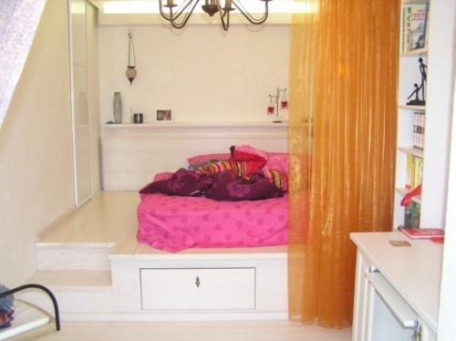 Platform alcove bed with steps, storage, and curtains
