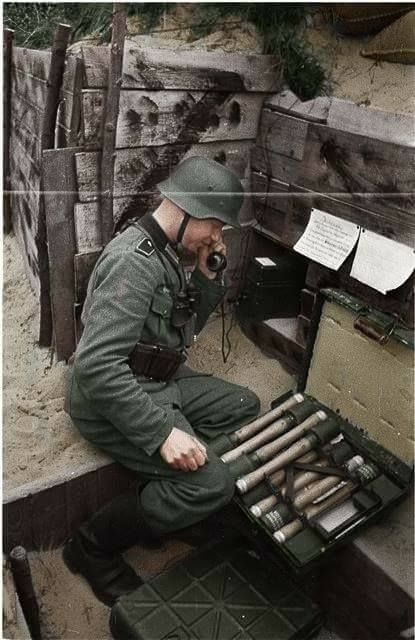 German soldier in a trench using a telephone and next to him we can see grenades.