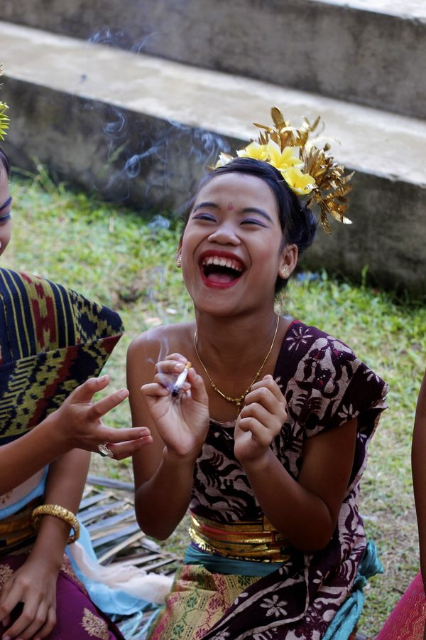 This is a tradition in Tenganan Dauh Tukad, Karangasem, Bali, Indonesia, where they allow girls of certain age to try the everyday adult things that they aren't usually allowed to have such as smoking. In this picture, a ten year old girl is trying cigarette.The reason they have this rite of passage is so that the kid will decide what is right and what is wrong for themselves.