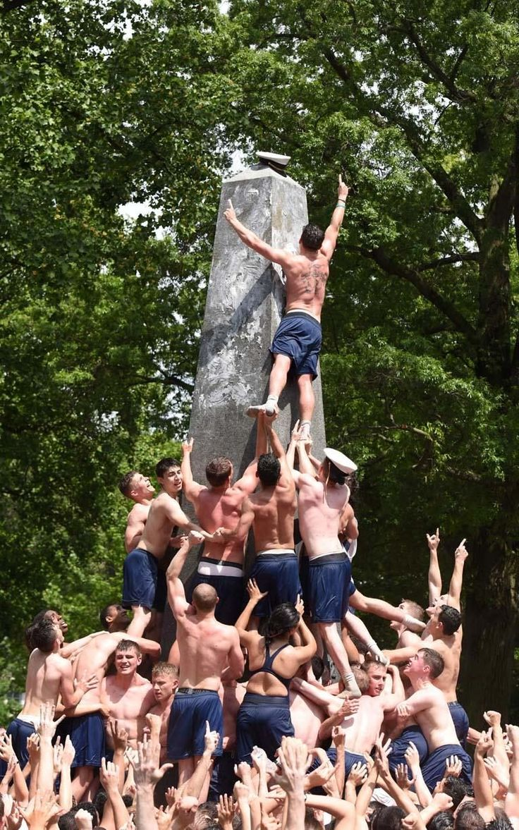 Plebes make a human wall to climb the Herndon Monument which is covered with vegetable fat at the U.S. Naval Academy (USNA) in Annapolis, Maryland