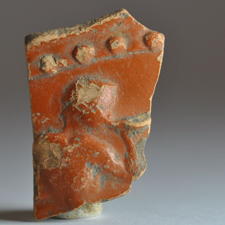 Arretine ware Samian ware shard with man playing tuba, 1st century A.D. 3.7 cm high. Private collection