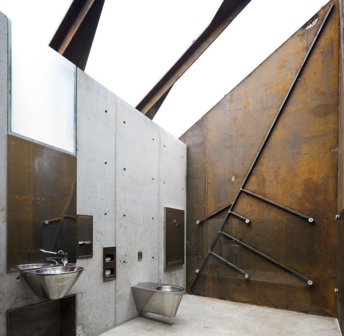 bathroom decor ideas, industrial style toilet, with concrete and rusty metal walls, plain silver colored metal sink and toilet seat, sloped ceiling with metal beam, supporting a clear glass surface