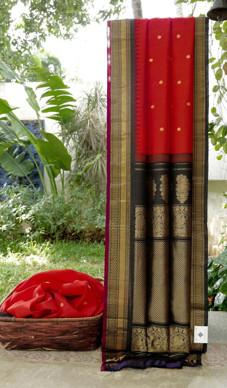 This gadwal silk is in ruby red with gold zari bhuttas. The border is in mulberry purple and black with gold zari work and the pallu is in black intricately woven with gold zari making it a traditi…