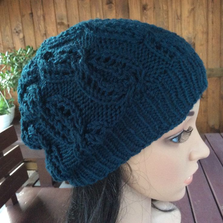 Turkusowa czapka zrobiona ażurowym wzorem warkoczowym.
