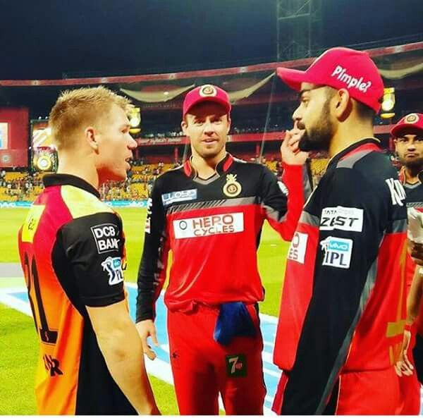 Caption time. Virat Kohli having some discussion with David Warner and AB de Villiers is photo bombing.