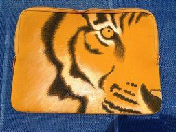 "Photo posted in an Amazon customer review for Stained by Sharpie markers. ""[The customer's daughter] used them to sketch a tiger on her orange laptop sleeve (using only the black) along with a separate pen, ""Marvy Uchida DecoFabric Marker, White"" to add the white highlights."""