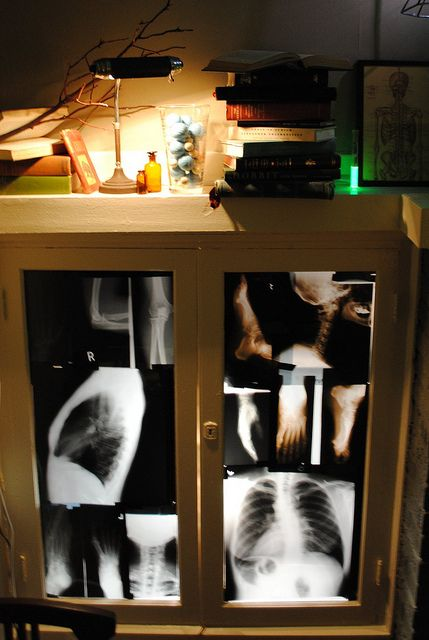 Purchase X-rays (available on eBay?), tape to insides of glass cabinets and back-light using battery-powered lanterns.