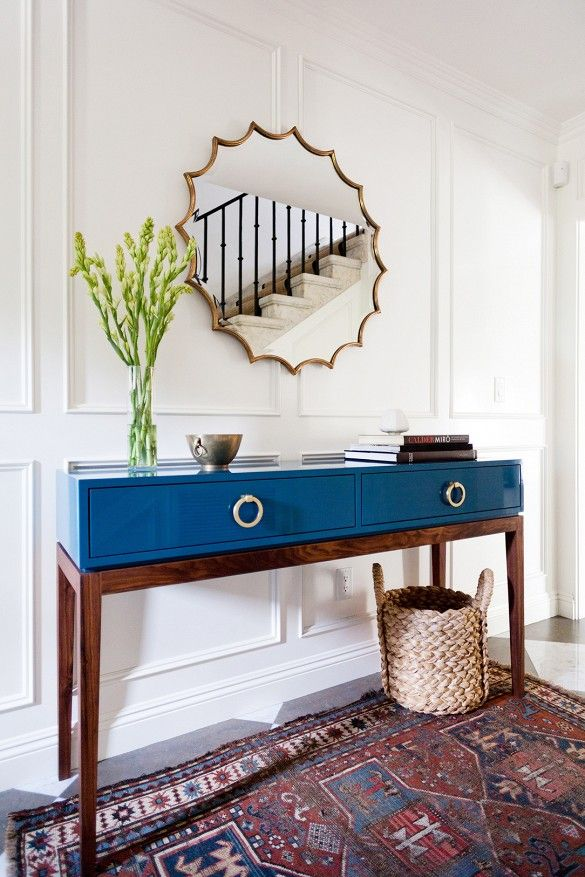 Blue console; white panelling; hallway