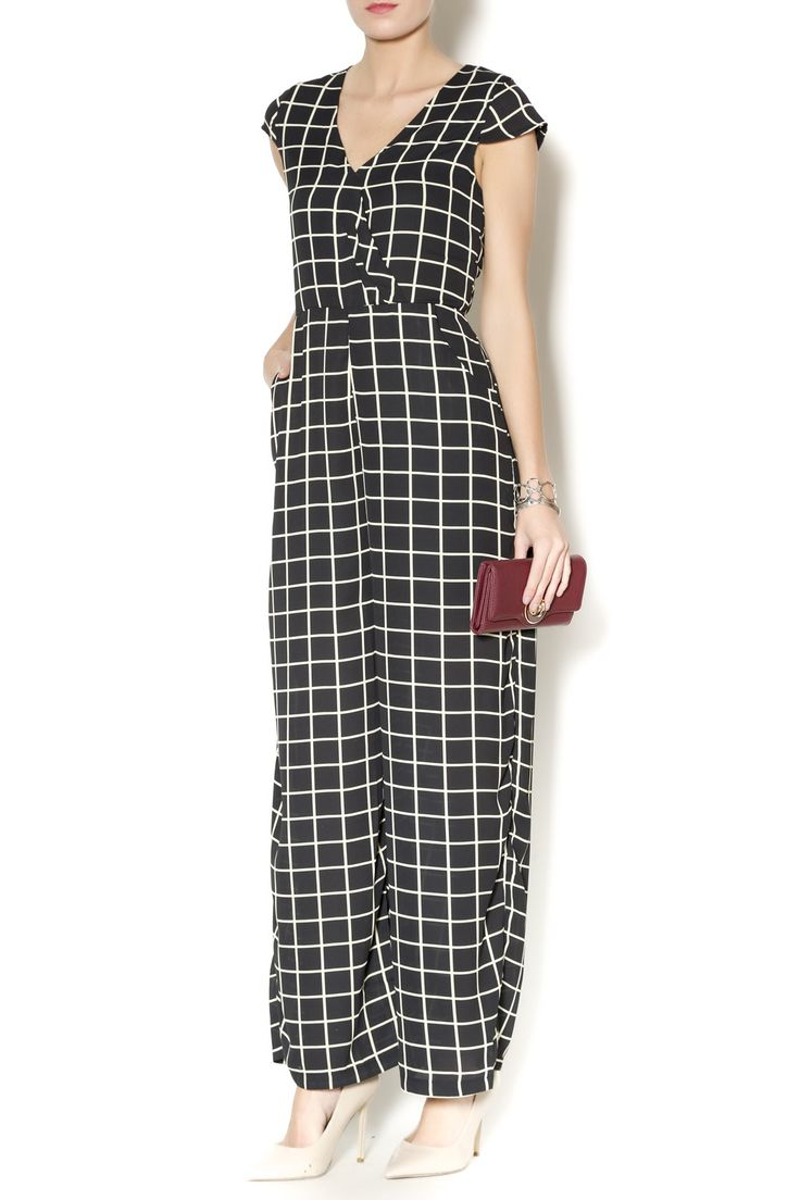 Black v-neck jumpsuit with sleeves and pockets. Ivory plaid detailing. Take this gorgeous jumpsuit from day to night with the switch of shoes and jewels!