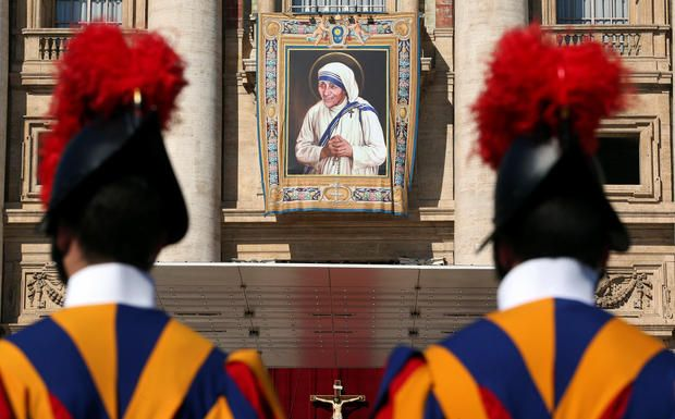 Swiss Guards stand in front of a tapestry depicting Mother Teresa of Calcutta before a mass, celebrated by Pope Francis, for her canonization in Saint Peter's Square